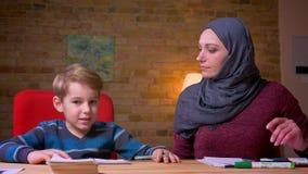 Moslemische Mutter im hijab, das zu Hause Hausarbeit mit ihrem kleinen Sohn am Tisch tut stock video footage