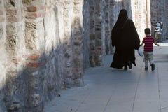 Moslemische Mutter und Sohn auf Bürgersteig am Morgen Stockfotos