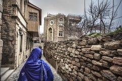 Moslemische traditionelle Frau, die alte historische Stadt in Baku Azerbaijan besichtigt Innrer-Stadt Lizenzfreie Stockbilder