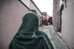 Moslemische traditionelle Frau, die alte historische Stadt in Baku Azerbaijan besichtigt Innrer-Stadt Lizenzfreies Stockfoto