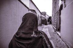 Moslemische traditionelle Frau, die alte historische Stadt in Baku Azerbaijan besichtigt Innrer-Stadt Lizenzfreies Stockbild