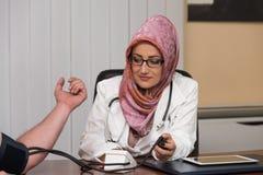 Moslemischen Blutdruck Doktor-Taking Young Mans lizenzfreie stockfotografie