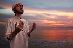 Moslemischer Mann beten auf dem Strand Stockbild