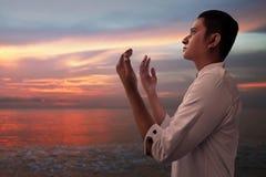 Moslemischer Mann beten auf dem Strand Lizenzfreies Stockbild