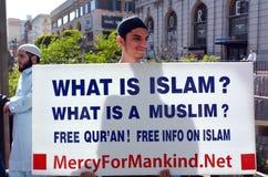 Moslemischer Mann hält, was Islamzeichen während eines Protestes ist Lizenzfreie Stockfotografie