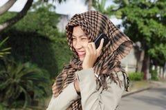 Moslemisches Mädchen, das durch Mobiltelefon benennt Stockbilder