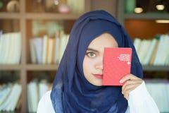 Moslemisches Mädchen, das einen Schweizer Pass zeigt stockfotos