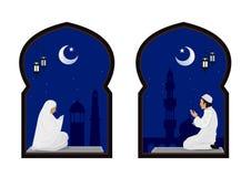 Moslemisches Mann- und Frauengebet nachts mit Moscheenhintergrund Lizenzfreies Stockbild