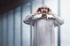 Moslemisches Mannhandeln adzan Stockfotografie