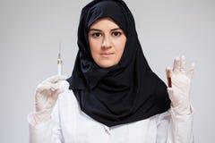 Moslemkrankenschwester, die Spritze hält stockbilder