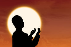 Moslems Silhouetteo f, die bei Sonnenuntergang beten lizenzfreies stockfoto