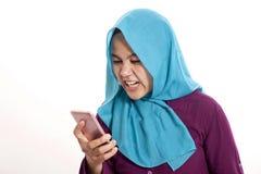 Moslim Boze Vrouw terwijl het Lezen van Sms-bericht op Smartphone royalty-vrije stock foto