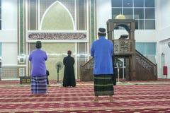 Moslim die bij een moskee bij nacht bidden stock fotografie