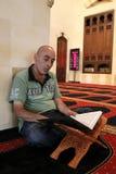 Moslim die het coranboek leest Stock Foto