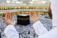 Moslim die in Mekkah met omhoog handen bidt Stock Afbeelding