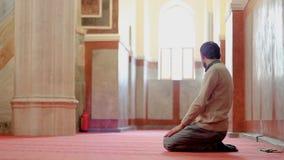 Moslim jong mannetje die in moskee bidden stock footage
