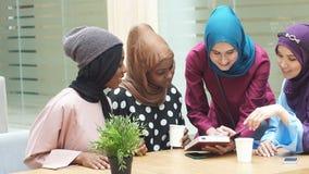 Moslim jonge vrouwen die van het diverse behoren tot een bepaald ras over nieuw boek van beroemde auteur spreken stock footage
