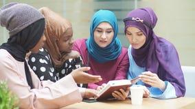 Moslim jonge vrouwen die van het diverse behoren tot een bepaald ras over nieuw boek van beroemde auteur spreken stock videobeelden