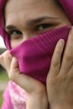 Moslim vrouw die en haar gezicht glimlacht verbergt Royalty-vrije Stock Foto's