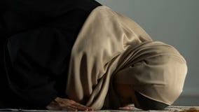 Moslim vrouwelijke zitting op het bidden deken en stil het spreken aan Allah, godsdienst stock videobeelden
