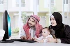 Moslimfamilie die computer online thuis met behulp van stock foto's