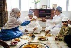 Moslimfamilie die diner op de vloer hebben stock afbeelding