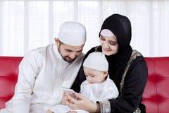 Moslimfamilie die slimme telefoon met behulp van stock foto