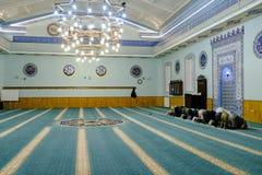 Moslimgroep die in een blauwe moskee bidden stock fotografie