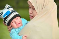 Moslimhijabimoeder die zijn schreeuwende zuigelingsbaby in haar wapen kalmeert bij openluchtpark in zonnige dag stock foto