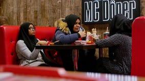 Moslimmeisjes in een restaurant die varkensvlees eten stock video
