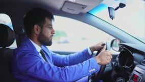 Moslimmens in blauw kostuum die de auto drijven Knappe ernstige zakenman stock footage
