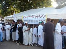 Moslims gaan door een tent aan een wegkant over Stock Afbeelding