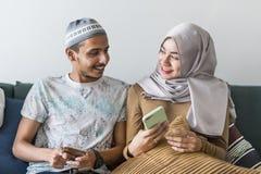 Moslimvrienden die sociale media op telefoons gebruiken stock afbeeldingen