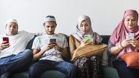 Moslimvrienden die sociale media op telefoons gebruiken stock foto's