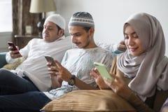 Moslimvrienden die sociale media op telefoons gebruiken stock foto