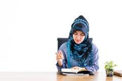Moslimvrouw die aan bureaulijst werken die op wit wordt geïsoleerd royalty-vrije stock afbeelding