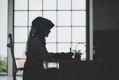 Moslimvrouw die aan het silhouet van de bureaulijst werken royalty-vrije stock foto