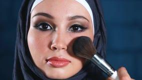 Moslimvrouw die make-up op haar gezicht met borstel doen stock video
