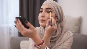 Moslimvrouw die make-up op haar gezicht met borstel doen Het moderne leven van moslimmensen Make-up thuis Zolder binnenlandse rui stock video