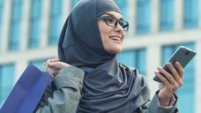 Moslimvrouw die naar verkoop in smartphone, Internet zoeken die, close-up winkelen stock video