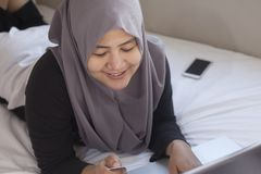 Moslimvrouw die Online Aankoop maken stock foto