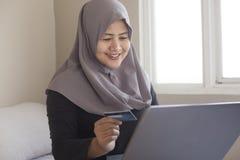 Moslimvrouw die Online Aankoop maken stock fotografie