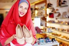 Moslimvrouw die schoenen in een winkel kiezen Stock Foto's