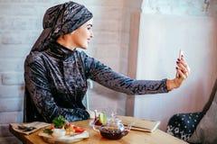 Moslimvrouw die selfie in koffie met smartphone nemen stock afbeelding
