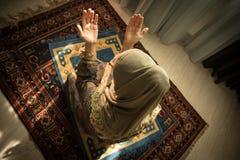 Moslimvrouw die voor de moslimgod van Allah bij ruimte dichtbij venster bidden Handen van moslimvrouw op het tapijt die in het tr stock afbeeldingen