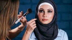 Moslimvrouw in hijab in schoonheidssalon Schoonheidsspecialist die make-up toepast stock video