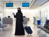 Moslimvrouw met kaartje, paspoort en reiszak Royalty-vrije Stock Foto's