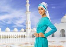 Moslimvrouw op witte moskeeachtergrond stock afbeelding