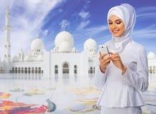 Moslimvrouw op witte moskeeachtergrond royalty-vrije stock afbeelding