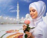 Moslimvrouw op witte moskeeachtergrond stock foto's